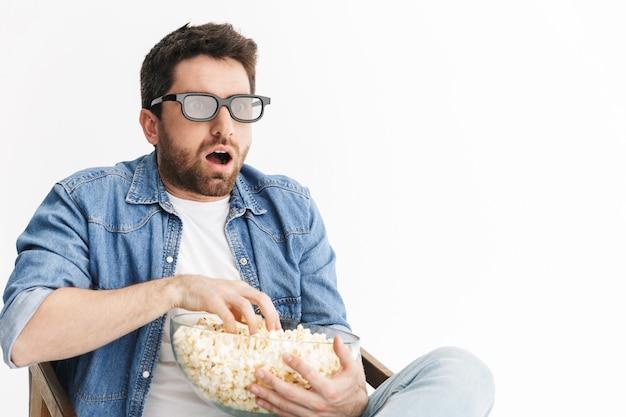 Portret zszokowanego, przystojnego brodatego mężczyzny w zwykłych ubraniach, siedzącego na krześle na białym tle, oglądającego film, jedzącego popcorn