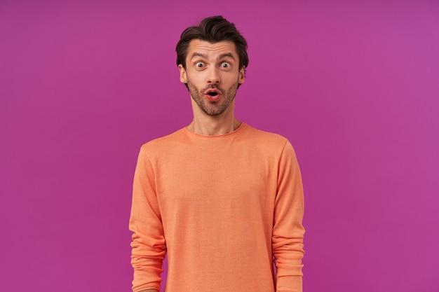 Portret zszokowanego, zaskoczonego mężczyzny z brunetką i włosiem. ubrana w pomarańczowy sweter z podwiniętymi rękawami