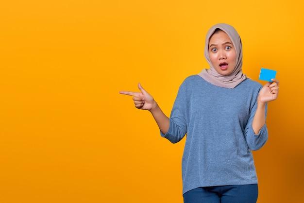 Portret zszokowanej azjatki trzymającej kartę kredytową i wskazującego palcem na pustą przestrzeń