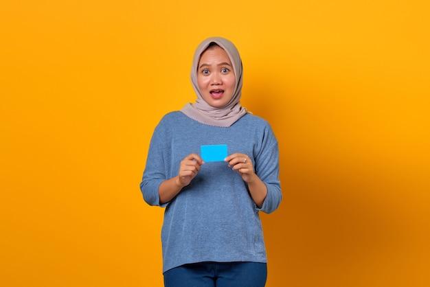 Portret zszokowanej azjatyckiej kobiety stojącej i trzymającej kartę kredytową na żółtym tle