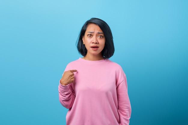 Portret zszokowanej azjatyckiej kobiety zadający pytanie i wskazujący na siebie na niebieskim tle