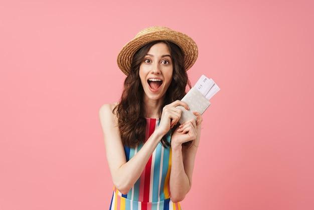 Portret zszokowanej emocjonalnej szczęśliwej młodej uroczej kobiety pozuje na białym tle nad różową ścianą trzymając paszport z biletami
