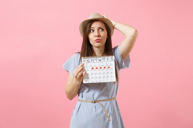 Portret zszokowanej kobiety w niebieskiej sukience, kapelusz trzymający kalendarz okresów do sprawdzania dni menstruacji na białym tle na jasnym, modnym różowym tle. medycyna, opieka zdrowotna, koncepcja ginekologiczna. skopiuj miejsce