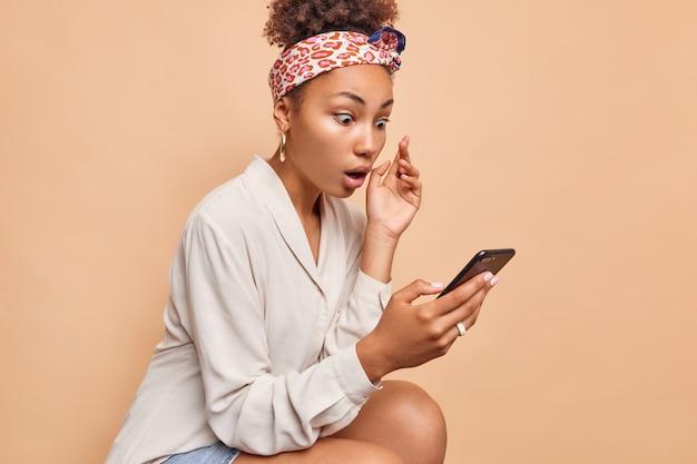 Portret zszokowanej kobiety z kręconymi włosami nosi opaskę na co dzień koszulę patrzy pod wrażeniem ekranu smartfona czyta zaskakujące powiadomienie nieoczekiwaną wiadomość na białym tle nad brązową ścianą wzdycha zdumiony