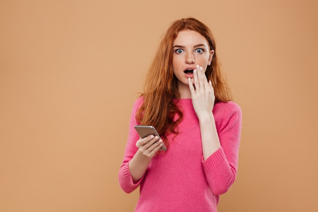 Portret zszokowanej ładnej rudowłosej dziewczyny