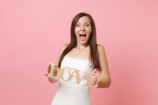 Portret zszokowanej podekscytowanej kobiety w koronkowej białej sukni stojącej i trzymającej drewniane litery słowa miłość