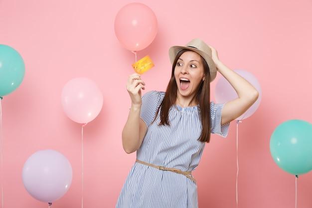 Portret zszokowanej szczęśliwej młodej kobiety w słomkowym letnim kapeluszu w niebieskiej sukience, trzymając kartę kredytową, trzymając się głowy na różowym tle z kolorowymi balonami. urodziny wakacje party ludzie szczere emocje.