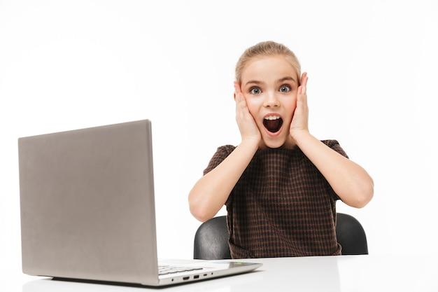 Portret zszokowanej uczennicy cieszącej się i używającej srebrnego laptopa siedząc przy biurku w klasie odizolowanej na białej ścianie