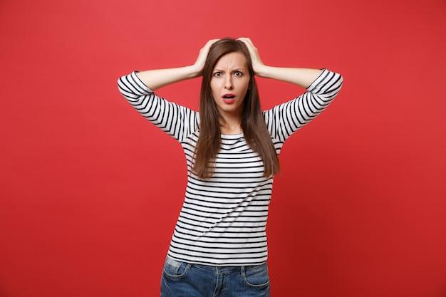 Portret zszokowanej, zakłopotanej młodej kobiety w pasiastych ubraniach, stojącej i kładącej ręce na głowie