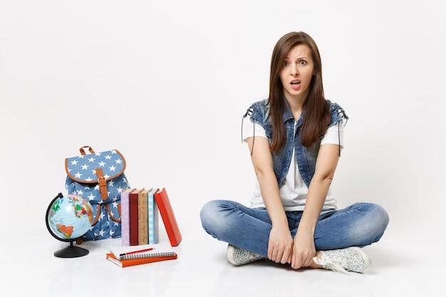 Portret zszokowanej zaniepokojonej studentki w dżinsowych ubraniach siedzącej w pobliżu kuli ziemskiej, plecaka, podręczników szkolnych na białym tle