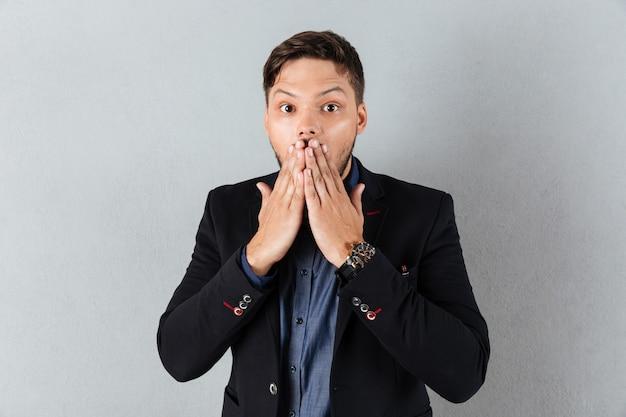 Portret zszokowany biznesmen obejmujące usta