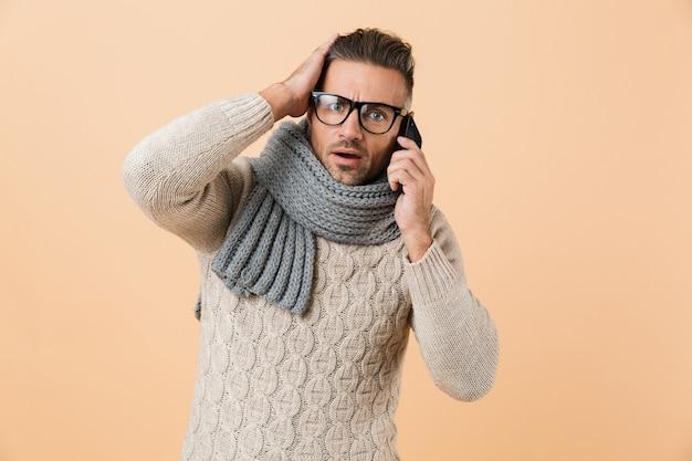 Portret zszokowany mężczyzna ubrany w sweter i szalik stojący na białym tle nad beżową ścianą, przy użyciu telefonu komórkowego