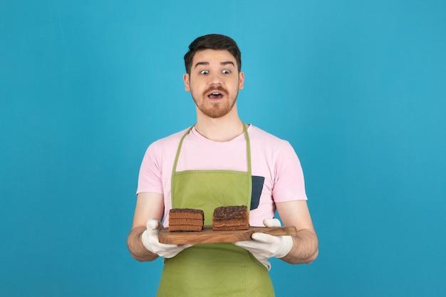 Portret zszokowany młody człowiek na niebieskim gospodarstwa plastry ciasta.