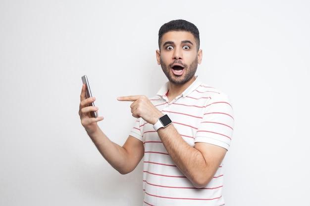 Portret zszokowany młody dorosły mężczyzna w białej koszulce stojącej, trzymający telefon i wskazujący palec z zaskoczoną twarzą i dużymi oczami. wewnątrz, na białym tle, studio strzał, białe tło, patrząc na kamerę