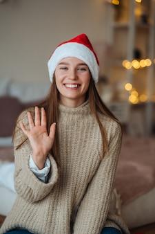 Portret życzliwej brunetki kobiety w kapeluszu santa macha podniesioną ręką i wita się z aparatem, ciesząc się świątecznym.
