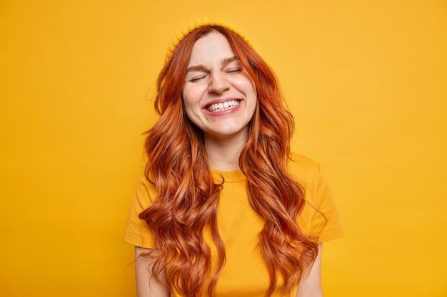 Portret żywej, radosnej rudej kobiety uśmiecha się, ma zamknięte oczy, ubrana w luźną koszulkę i kapelusz, pokazuje autentyczne emocje. stoi zrelaksowany nad żółtą ścianą. strzał monochromatyczny