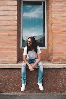 Portreta atrakcyjny mężczyzna blisko okno na miastowej scenie