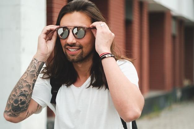 Portreta atrakcyjny mężczyzna z okularami przeciwsłonecznymi na miastowy sceny ono uśmiecha się