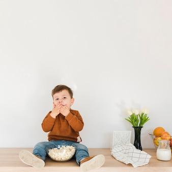 Portreta chłopiec łasowania popkorn