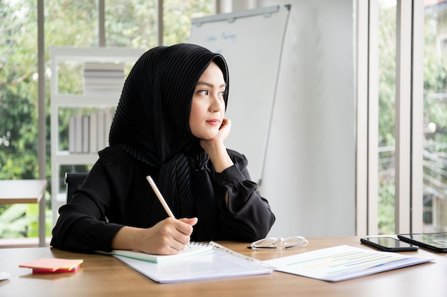 Portreta mądrze piękny azjatycki muzułmański bizneswoman pracuje w biurze, różnorodność kulturowa i płeć.