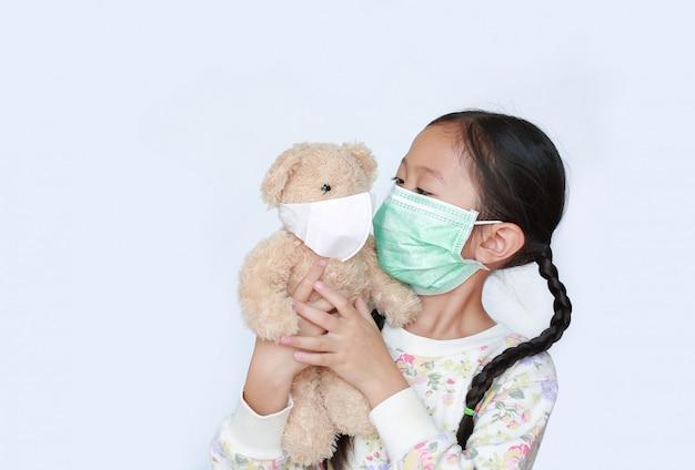 Portreta małego dziecka dziewczyny mienia azjatykci miś z być ubranym medyczną ochronną maskę na białym tle wpólnie