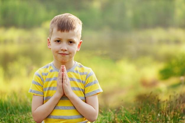 Portreta małego ślicznego chłopiec ćwiczy joga poza w wiosna dniu