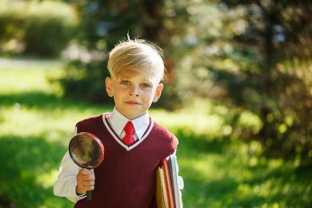 Portreta mały uczeń na naturze. dziecko z książkami i lupą. edukacja dla dzieci. powrót do koncepcji szkoły