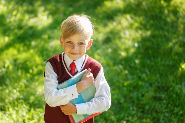 Portreta mały uczeń na naturze. dziecko z książkami i ubrany mundur. edukacja dla dzieci. powrót do koncepcji szkoły.