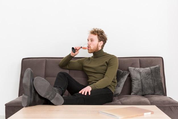Portreta młody człowiek pije wino