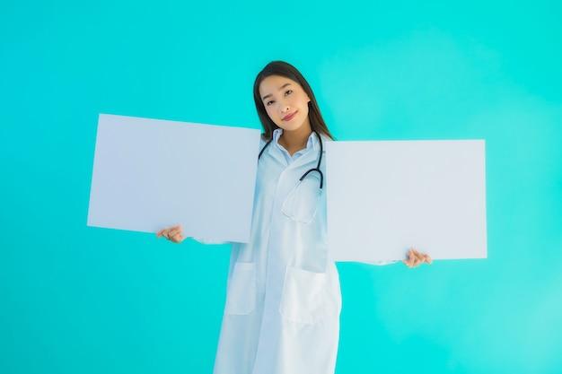 Portreta piękna młoda azjata lekarki kobieta z pustym plakatem