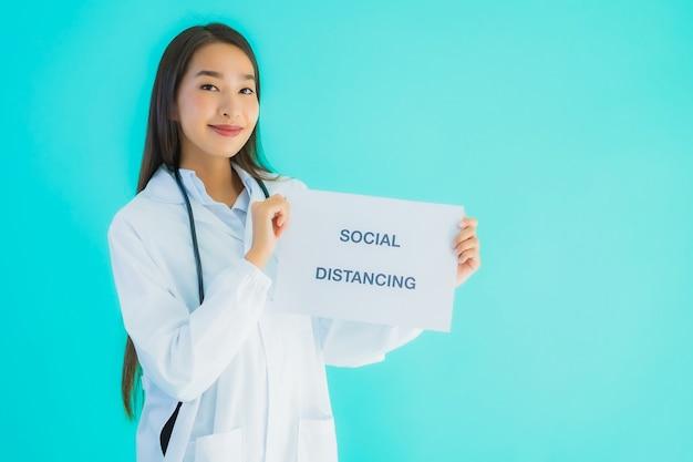 Portreta piękna młoda azjata lekarki kobieta z znaka papierem z ogólnospołecznym dystansowaniem