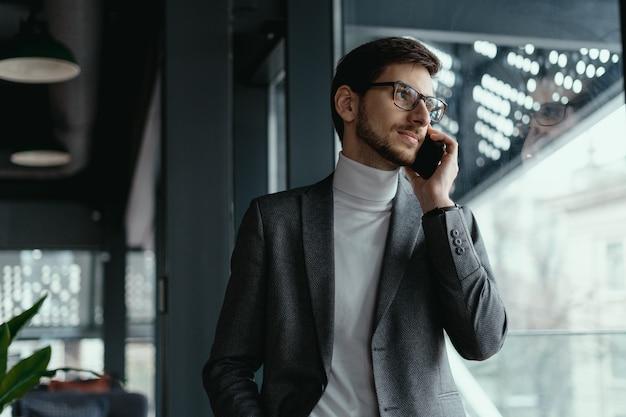 Portreta pomyślny biznesowy mężczyzna opowiada na smartphone