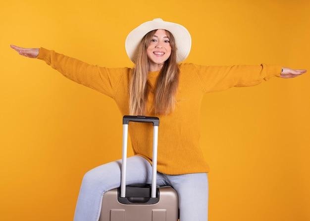 Portreta portret szczęśliwa powabna kobieta z jej walizką, ponieważ jedzie na wycieczkę, kolor żółty przestrzeń