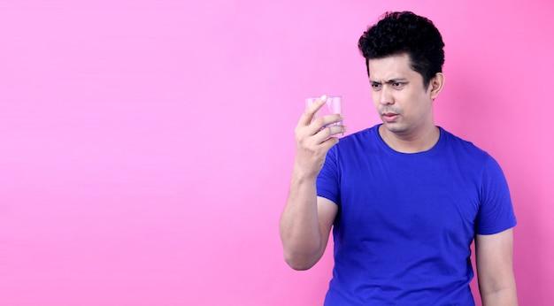 Portreta przystojni azja mężczyzna chcą przestać pić alkohol na różowym tle w studiu