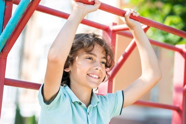 Portreta smiley chłopiec bawić się w parku