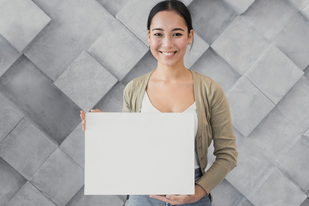 Portreta smiley młoda kobieta przy biurem