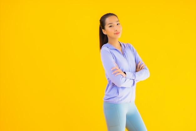 Portreta sporta piękna młoda azjatykcia kobieta przygotowywająca dla ćwiczenia na kolorze żółtym