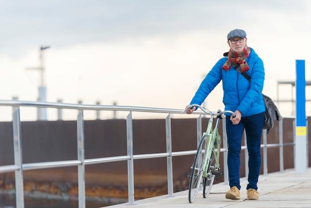 Portreta starszego mężczyzna odprowadzenie z jego bicyklem w ulicie