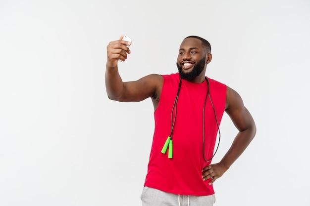 Portreta szczęśliwy młody afrykański mężczyzna pozować odizolowywam nad popielatym bierze selfie telefonem z arkaną i sport odzieżą.
