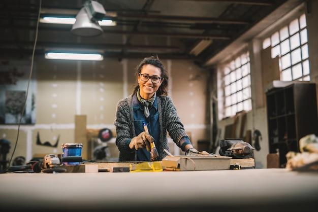 Portreta widok szczęśliwy atrakcyjny fachowy żeńskiego pracownika obrazu drewno z czarnym kolorem w pogodnym warsztacie
