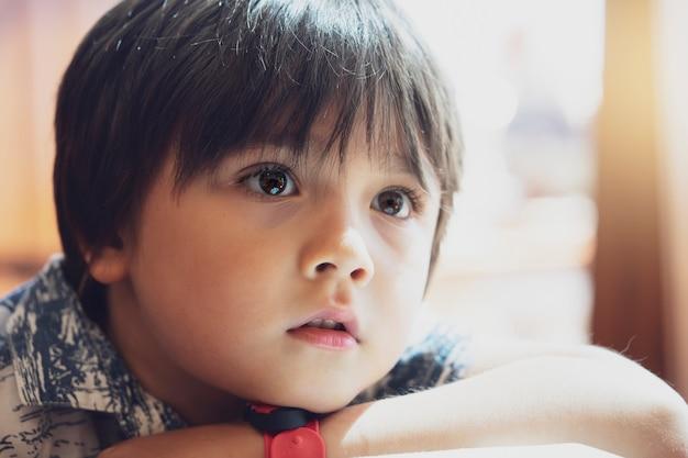Portretowy dzieciak zagubiony w myśleniu wyglądający przez okno z jasnym porannym światłem