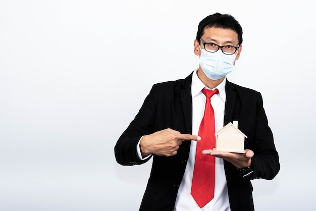 Portretowy obraz azjatyckiego biznesmena trzymającego i pokazującego model domu na białym tle