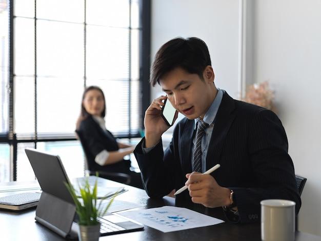 Portrety biznesmen rozmawia przez telefon podczas pracy z dokumentacją w biurze
