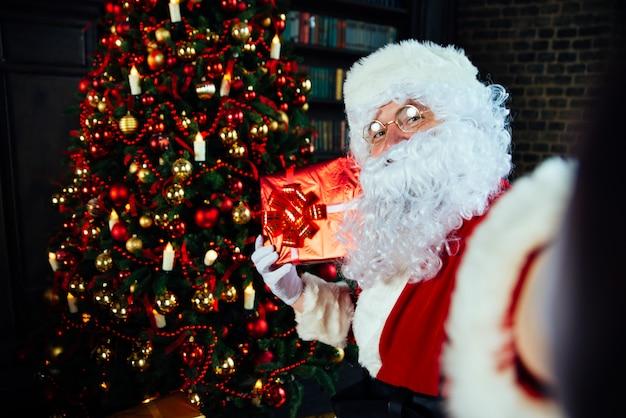 Portrety i styl życia świętego mikołaja. robienie selfie z świątecznych dekoracji