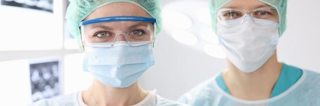Portrety lekarzy chirurgów w odzieży ochronnej w klinice
