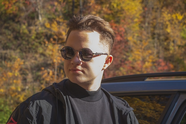 Portrety młodego faceta w jesiennym lesie.