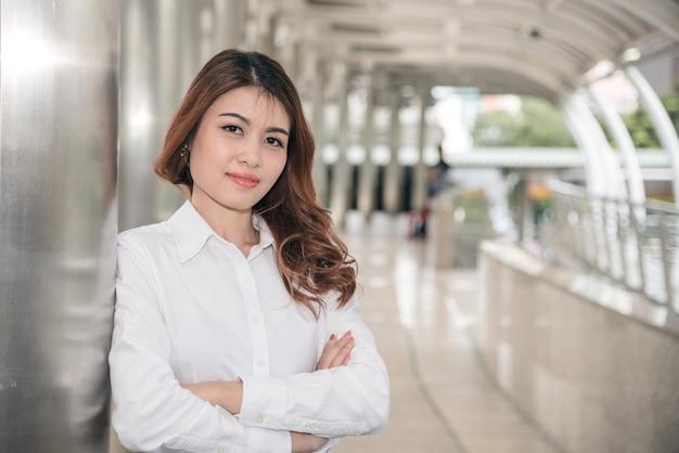 Portrety piękny azjatykci kobiety spojrzenie rozochocony i zaufanie stoi w outdoors
