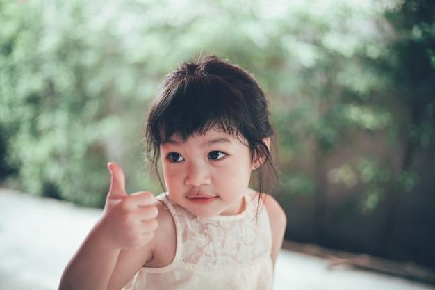 Portrety szczęśliwa azjatycka dziewczyna patrząc na kamery na zewnątrz.
