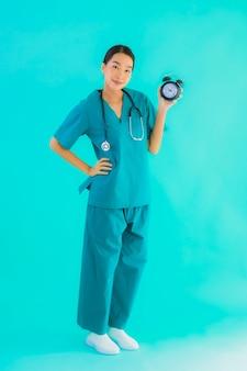 Portriat piękny młody azjatycki lekarz kobieta pokaż zegar lub alarm