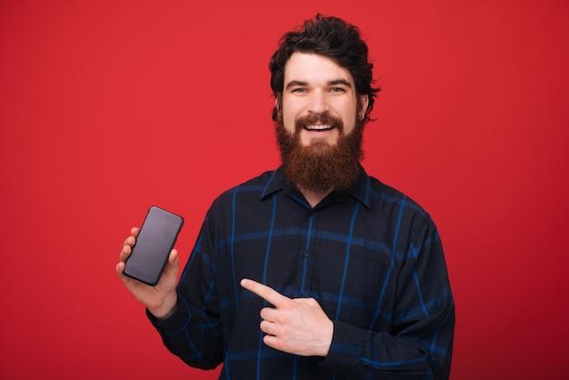 Portrit przystojnego mężczyzny z brodą pijącą na telefon komórkowy, podczas gdy nad czerwoną ścianą